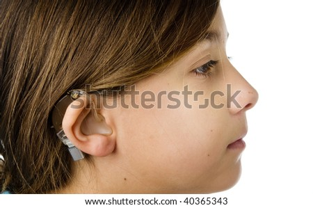 Young girl wearing a hearing aid - stock photo