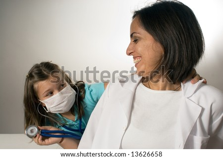 Young girl wearing a mask listens to the smiling doctor's heartbeat. They are having fun and being playful. Horizontally framed photograph - stock photo