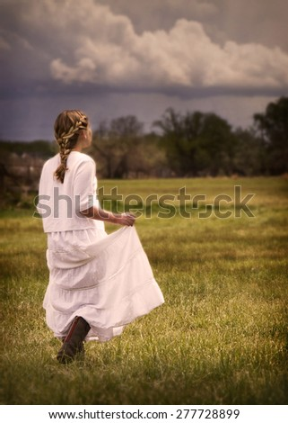 Young girl wearing a white dress walking in a pasture or prairie on a rainy cloudy day. - stock photo