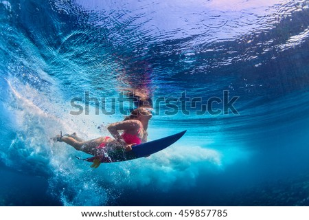 Young girl wearing bikini in action - surfer with surf board dive underwater under ocean wave. Family lifestyle, people water sport adventure camp and beach extreme swim on summer vacation with child.