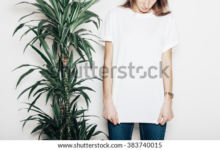 Young girl wearing blank t-shirt. Concrete wall background and green palm close the girl. Horizontal mockup - stock photo