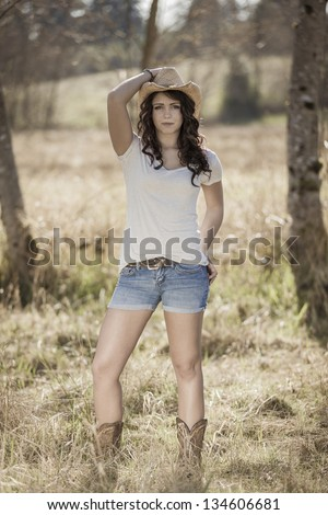 Young girl wearing cowboy hat and boots - stock photo