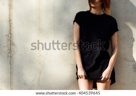 young girl wearing in a black blank t-shirt standing on a background of concrete wall. Sun rays - stock photo