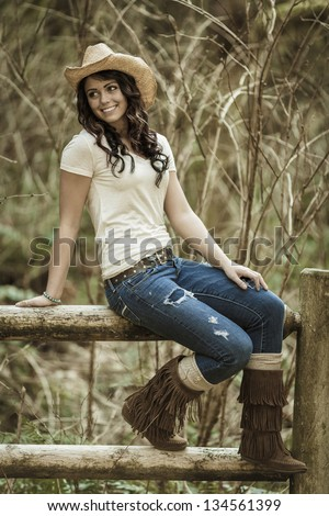 Young girl wearing jeans and white shirt sitting on the fence - stock photo