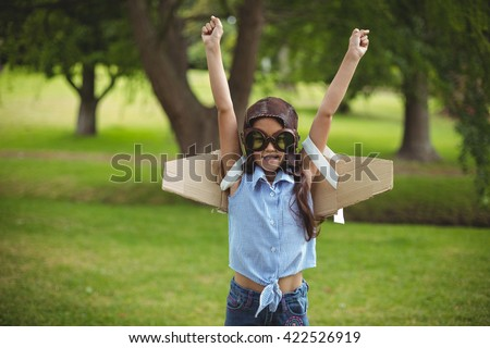 Young girl wearing leather pilot helmet and wings pretending to fly in garden - stock photo