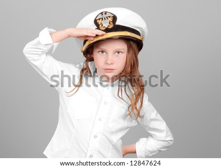 Young girl wearing Navy officer's hat saluting - stock photo