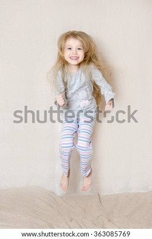 Young Girl Wearing Pajamas Jumping On Bed - stock photo