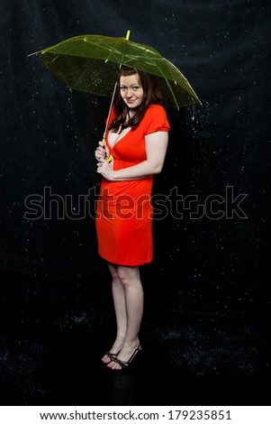 Young girl wearing red dress stands under an umbrella - stock photo