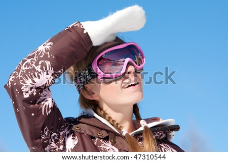 Young girl wearing ski mask on winter resort in Alps - stock photo