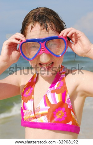 young girl wearing snorkeling mask at pretty beach