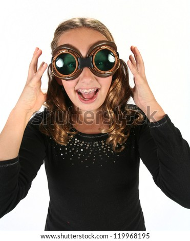 Young girl wearing steam punk goggles posing and screaming - stock photo