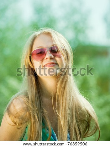 young girl wearing sunglasses against nature - stock photo