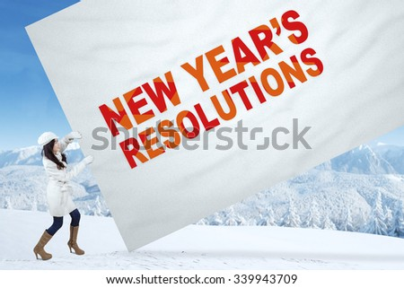 Young girl wearing winter fashion pulling a big poster with written of new year's resolutions