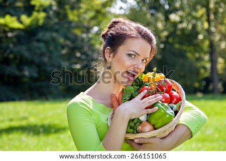 Young girl with a basket of different vegetables outdoors - stock photo