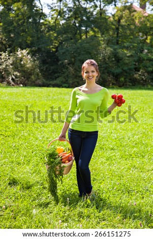 Young girl with a basket of vegetables and fruits outdoors - stock photo