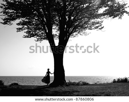 Young girl with a beautiful tree reflected in a puddle - stock photo
