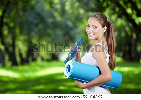 Young girl with a bottle of water and gym mat in the park - stock photo