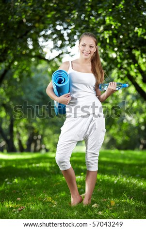 Young girl with a bottle of water and gymnastic mat - stock photo