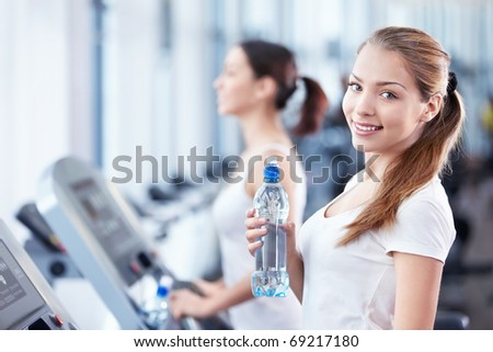 Young girl with a bottle of water on the treadmill - stock photo