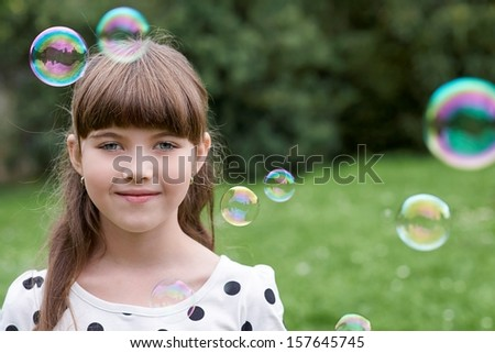 Young girl with a bubble by bubble blower