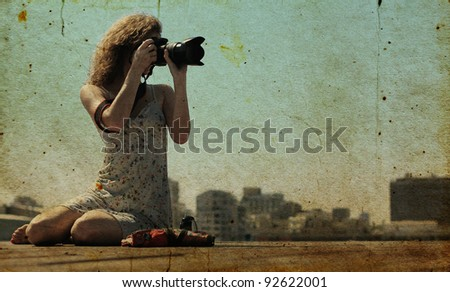 young girl with a camera.  Photo in old color image style. - stock photo