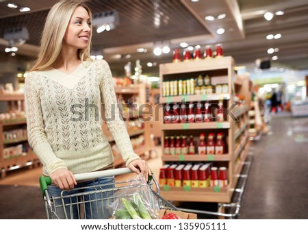Young girl with a cart in the store - stock photo