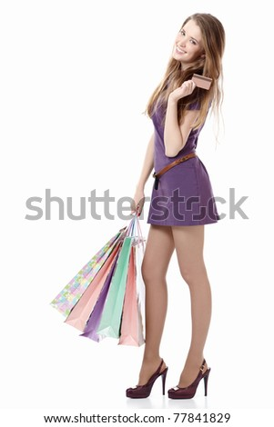 Young girl with a credit card and shopping bags on white background