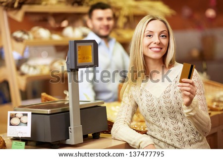 Young girl with a credit card at the store - stock photo