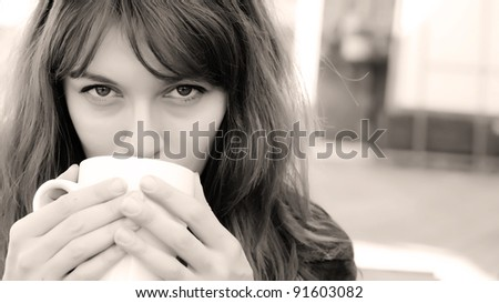 young girl with a cup of coffee. Focus on the eyes.