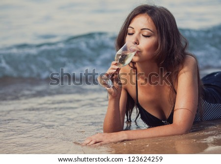 Young girl with a glass of champagne on the beach - stock photo