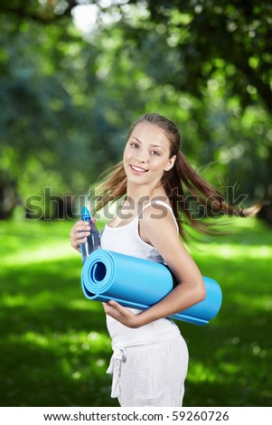 Young girl with a gym mat and a bottle of water in the park - stock photo