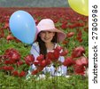 Young girl with a hat and blue balloon in a red flowers field - stock photo