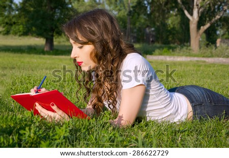 Young girl with a notepad and pen in a summer park on the grass