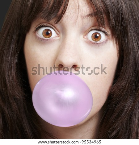 young girl with a pink bubble of chewing gum against a black background - stock photo