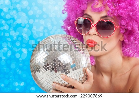 young girl with a pink wig holding a disco ball