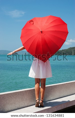 young girl with a red umbrella sits on the waterfront and looks at the sea