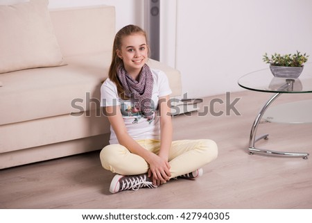 young girl with a smile, sitting on the couch at home, a schoolgirl and a student rests