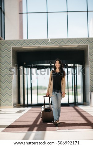 young girl with a suitcase goes on the terminal