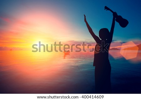 Young girl with a ukulele raised her hands up against the sea and the sunset sky