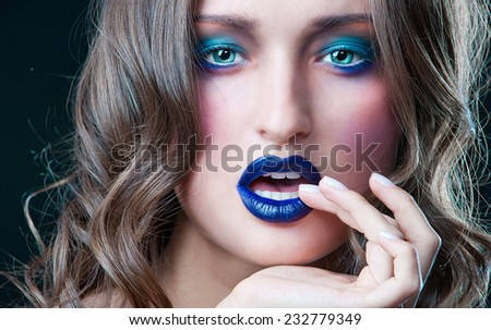 Young girl with an unusually beautiful makeup. Dark blue lips. Blue eyeshadow. - stock photo