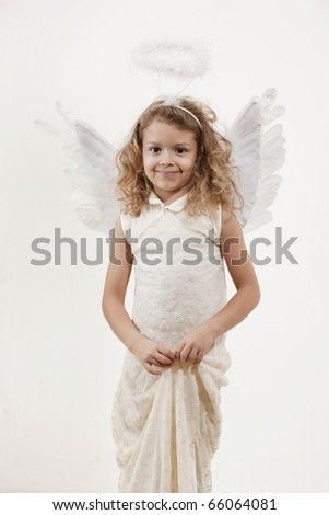 Young girl with angel wings in studio - stock photo