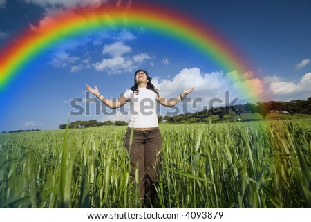 young girl with arms wide open contemplating the rainbow - stock photo