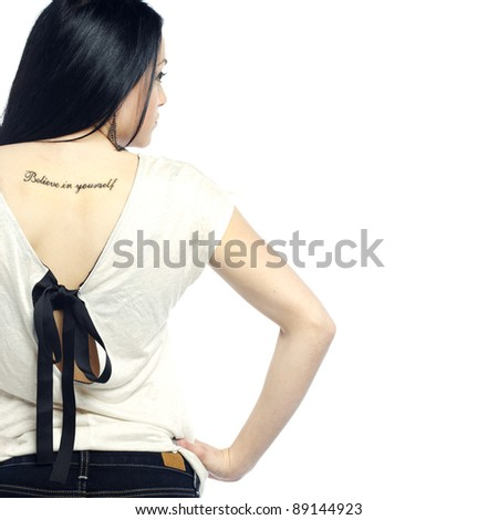 Young girl with back turned showing tattoo dressed for summer - stock photo