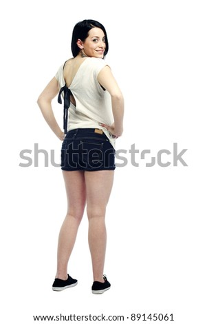 Young girl with back turned smiling dressed for summer against isolated background - stock photo