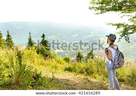 Young girl with backpack in mountain. - stock photo