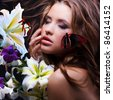 Young girl with beautiful face closed eyes surrounded by flowers and tropical butterfly sitting on her cheek - stock photo