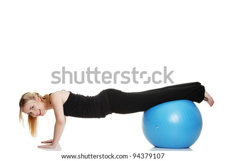 Young girl with big blue fit ball, isolated on white background