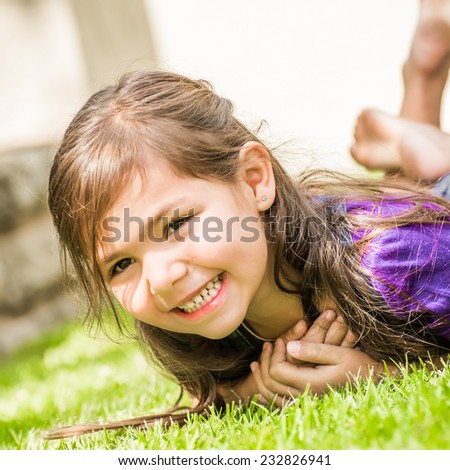 Young girl with big smile showing of her teeth, lying on the lawn of the back garden on a nice summer day. - stock photo