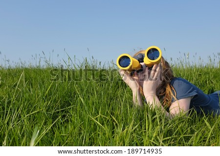 Young girl with binoculars in a meadow searching the sky - stock photo