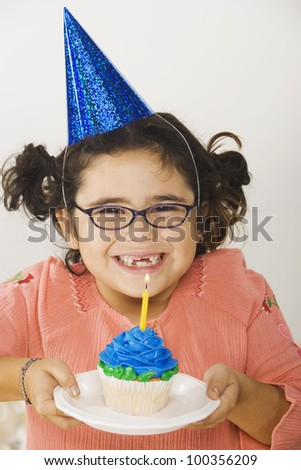 Young girl with birthday cupcake